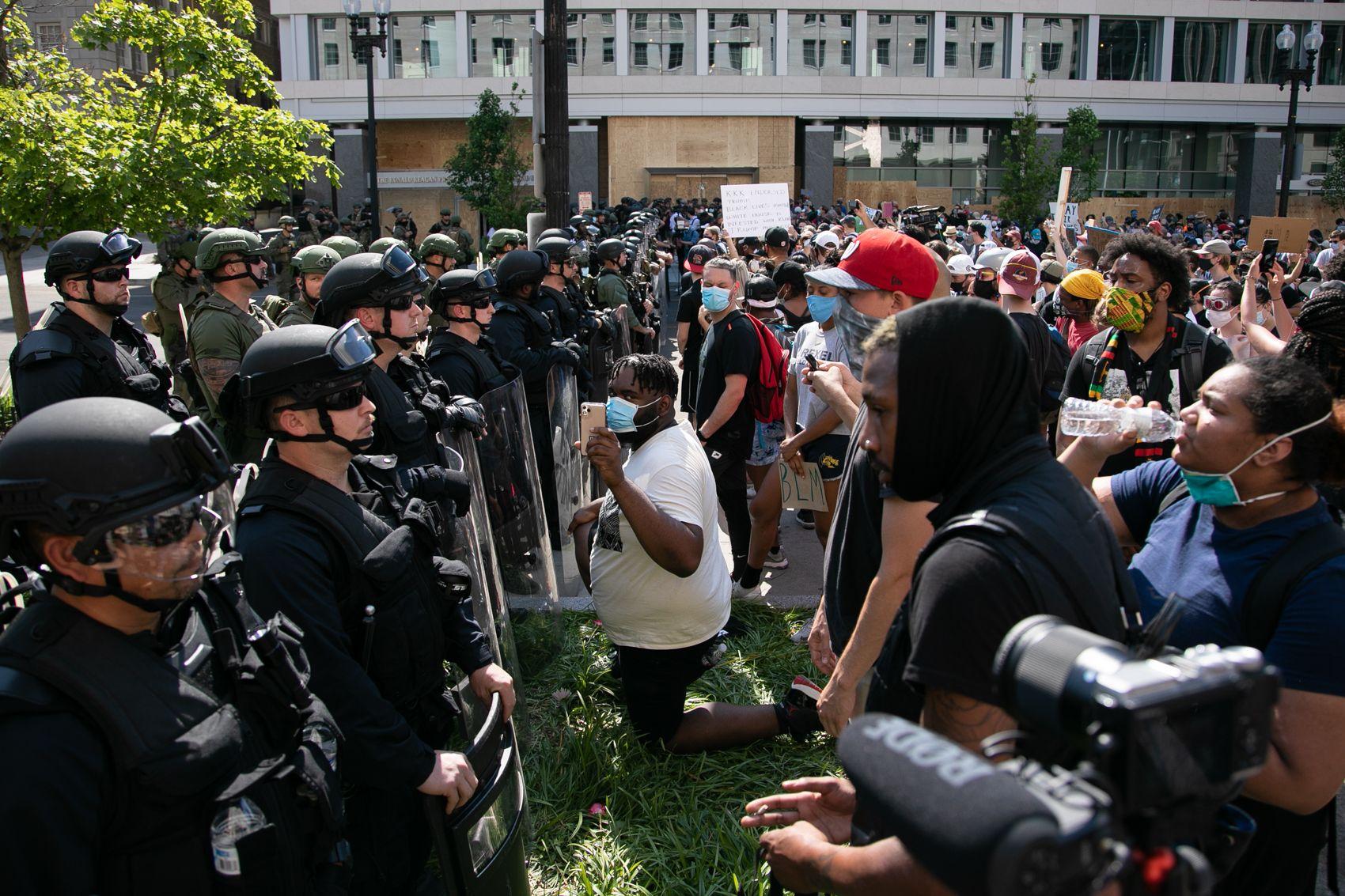 写真・図版 : ホワイトハウス周辺を警備する警官隊と抗議運動をする人たち=ワシントン、ランハム裕子撮影、2020年6月3日