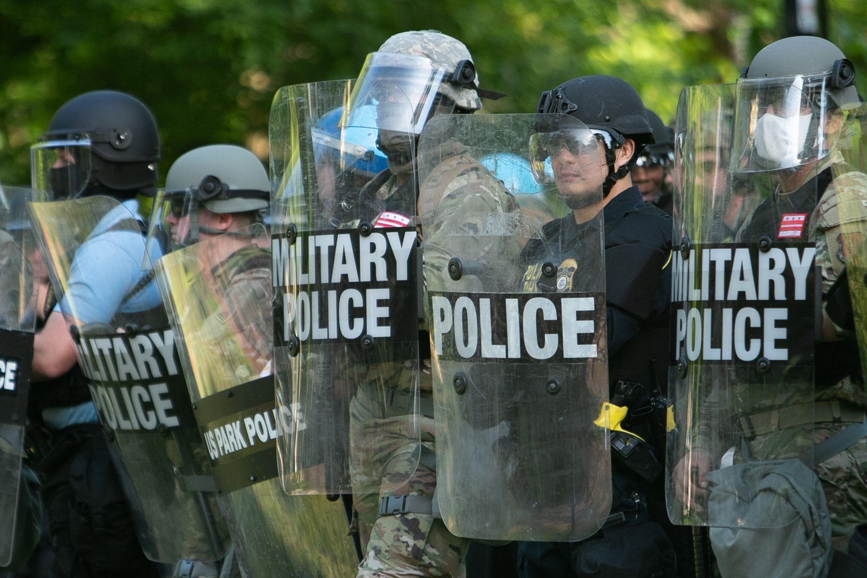 写真・図版 : ホワイトハウスの前で盾を持ち、一列に並ぶ警官隊=ワシントン、ランハム裕子撮影、2020年6月1日
