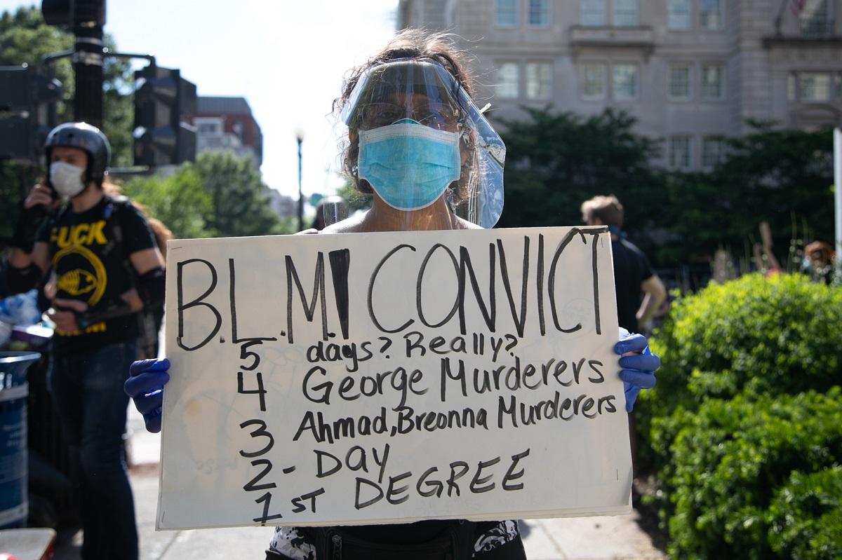 写真・図版 : フェイスガードとマスクを装着し、ホワイトハウス周辺で抗議デモに参加するアイシャ・コルベットさん=ワシントン、ランハム裕子撮影、2020年5月31日