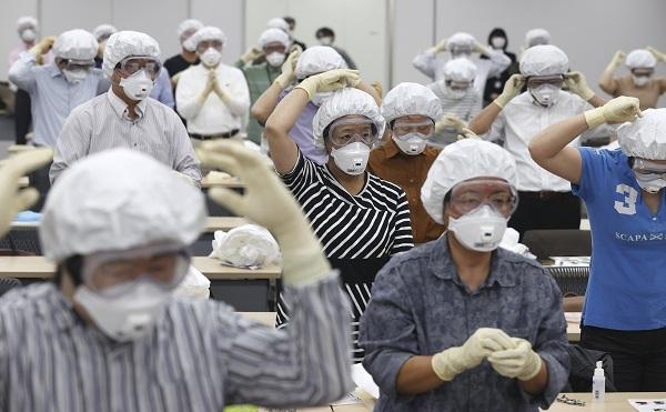 写真・図版 : 新型コロナウイルスの感染者らの診療のため、防護服の着脱の訓練をする医師たち=2020年5月1日、東京都千代田区、池田良撮影