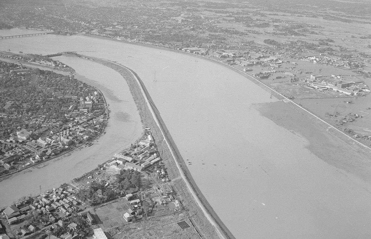 写真・図版 : 1958年9月、台風21号の大雨で増水した荒川(右)と隅田川。荒川左岸の河川敷にあった都民ゴルフ場はすべて水没した=現・東京都足立区新田1丁目の上空から