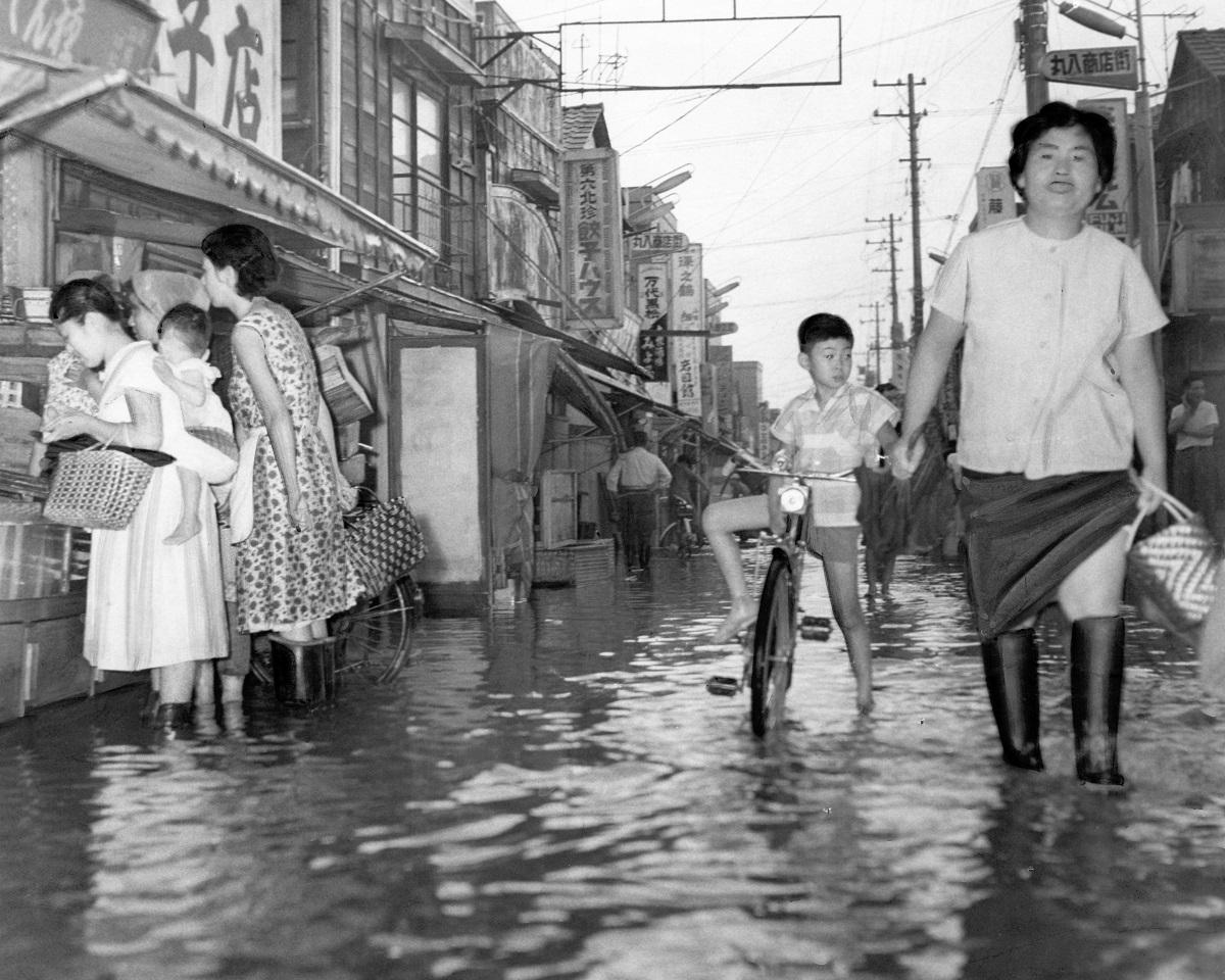 写真・図版 : 1964年東京五輪開幕のちょうど1年前、江東区の丸八通り。わずかな雨でもすぐに水が出た=1963年10月10日
