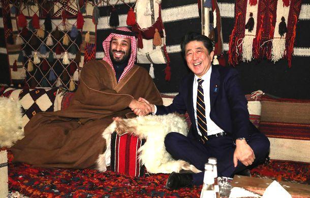 写真・図版 : サウジアラビアのムハンマド皇太子(左)の別荘地にある特設テントで歓迎を受け握手を交わす安倍晋三首相=2020年1月12日、サウジアラビアのウラー郊外