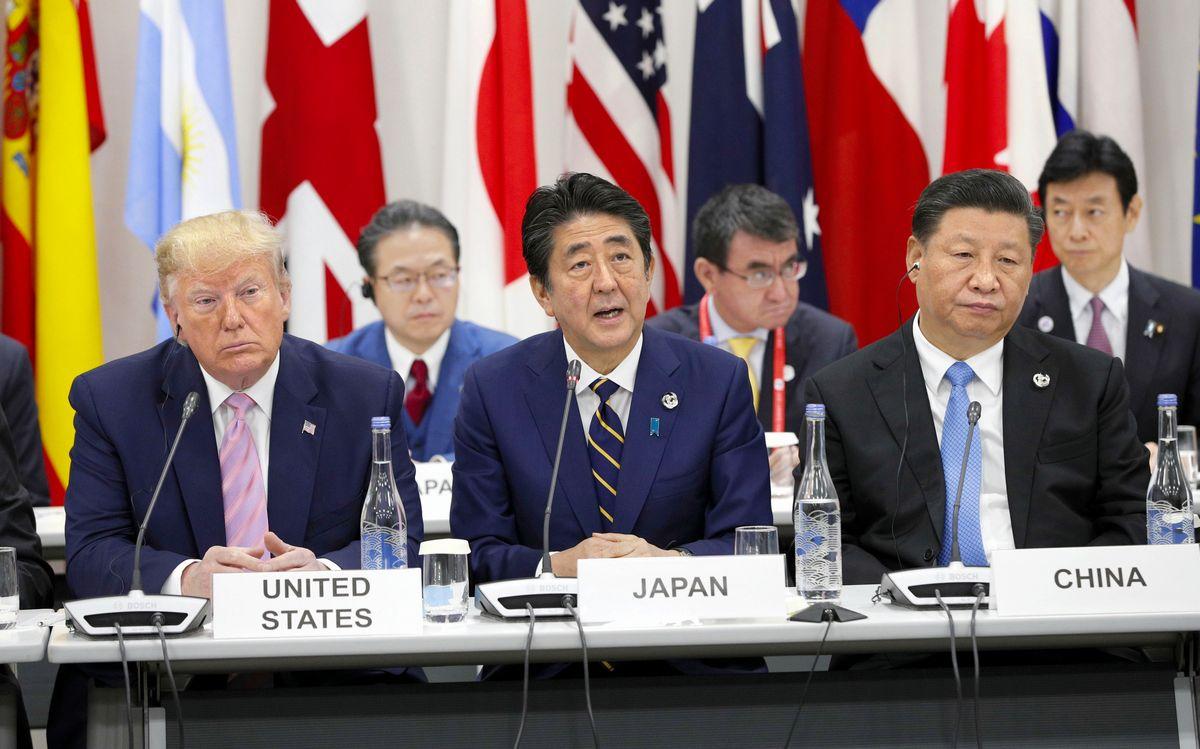 写真・図版 : 2019年6月、大阪でのG20サミットで司会をする安倍首相。左は米国のトランプ大統領、右は中国の習近平国家主席=大阪市住之江区。代表撮影