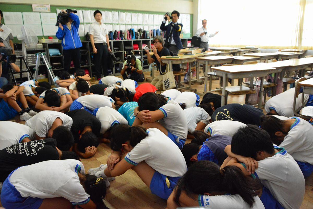 写真・図版 : 2017年7月のミサイル避難訓練で、教室の隅に集まり身を守る小学生ら=富山県高岡市の伏木小学校。朝日新聞社