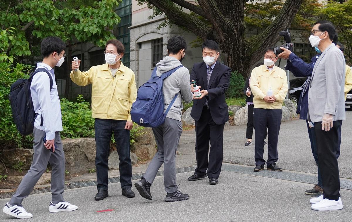 写真・図版 : ソウルの高校では、教職員が登校する生徒の体温を測定し、消毒液を手につけていた=2020年5月
