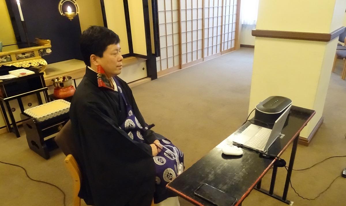 写真・図版 : オンラインで参列者とパソコンの画面越しに話す僧侶=2020年5月、提供・築地本願寺