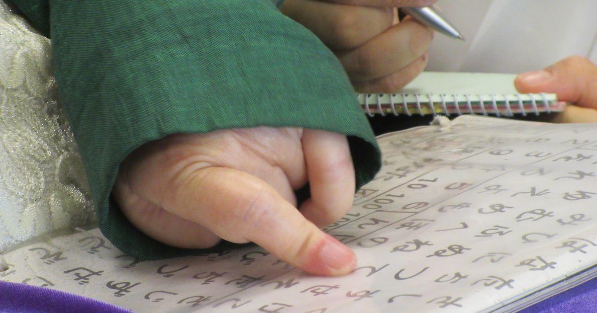 写真・図版 : 文字盤を指さして質問に答える三井絹子さん=2020年5月28日、東京・永田町の参議院議員会館