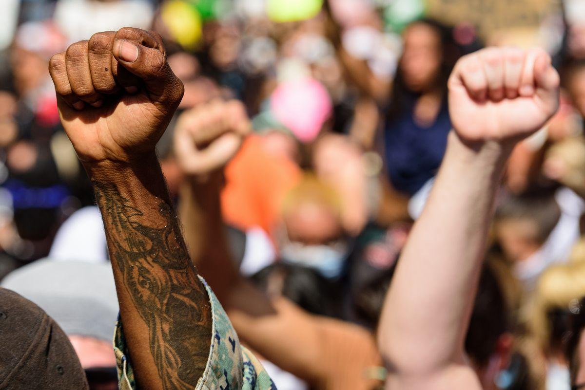 拳をつきあげて人種差別に抗議する人たち=2020年5月31日、米マイアミ、Tverdokhlib/shutterstock.com
