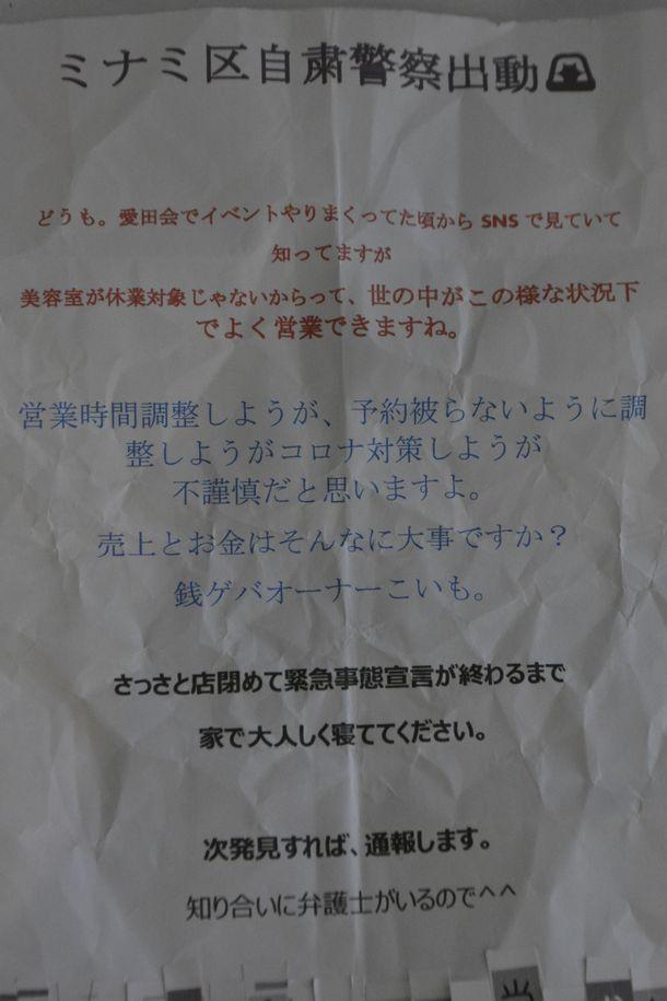 写真・図版 : 「ミナミ区自粛警察出動」などと書かれた貼り紙。ヘア-サロンの入り口に貼られていた=大阪市中央区