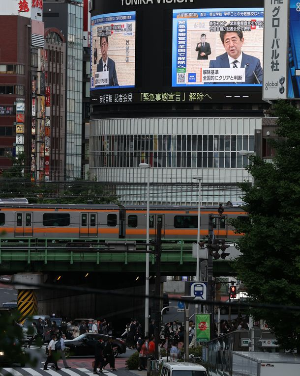 写真・図版 : 緊急事態宣言の解除について説明する安倍晋三首相が大型ビジョンに映し出された=2020年5月25日午後6時2分、東京・新宿