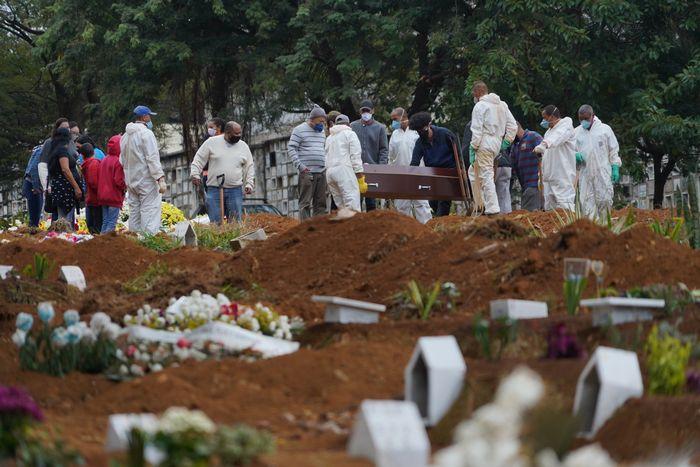 写真・図版 : ブラジル・サンパウロの墓地では、次々と運び込まれるひつぎを埋葬するために、いくつもの新しい穴が掘られていた=2020年5月15日、岡田玄撮影