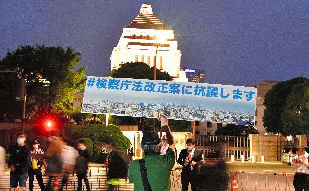 国会前でプラカードを掲げて検察庁法改正案に抗議する男性=5月15日、東京都千代田区