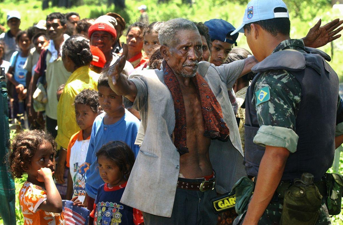 写真・図版 : 2002年3月、東ティモールに戻る難民たちを検問する国連PKOの隊員(右端)=東ティモール・バトゥガデ。朝日新聞社