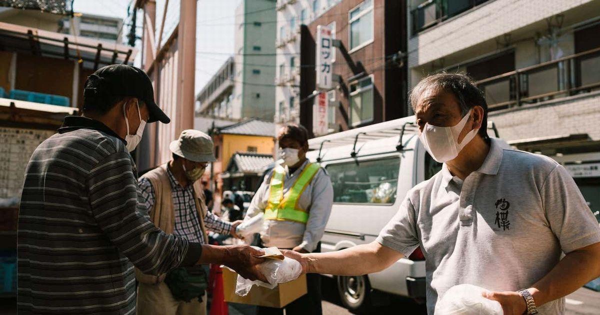 写真・図版 : 困窮者支援の最前線で働く人々にマスクを配布する奥田さん(右)。ステイホームが呼びかけられる中、医療従事者や困窮者支援など福祉に携わるソーシャルワーカーはそうはいかない。「私たちがステイホームできるのは、その最中でも外で体を張って働いている人がいるからだ」
