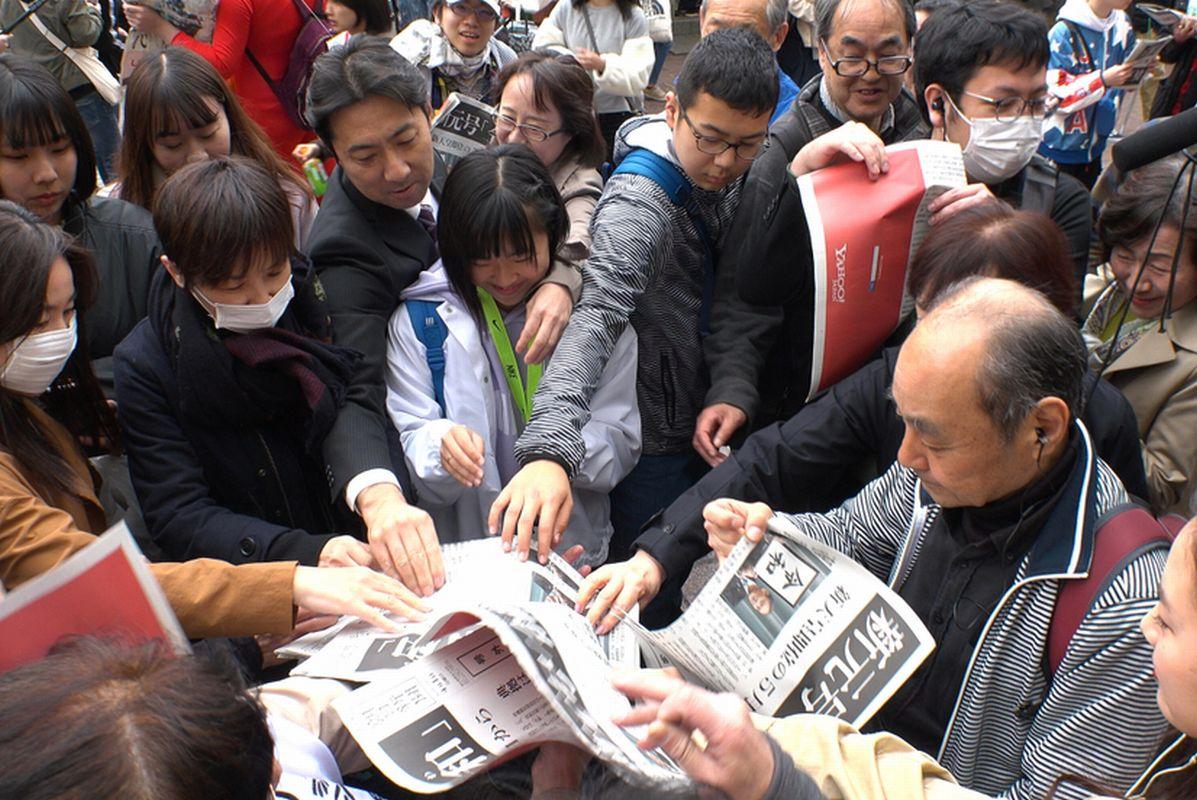 写真・図版 : 新元号「令和」の決定を伝える新聞の号外の配布に殺到する人たち