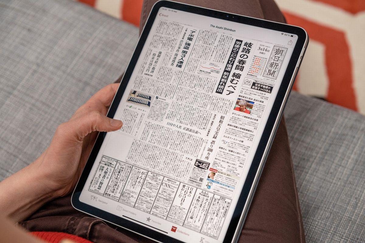 写真・図版 : タブレット端末で新聞のデジタル版を読む人(Hadrian/shutterstock)