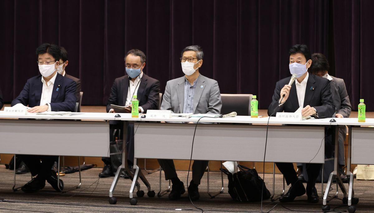 写真・図版 : 新型コロナウイルス感染症対策分科会の冒頭、あいさつする西村康稔経済再生相(前列右)。同中央は尾身茂分科会長、同左は加藤勝信厚労相=2020年7月6日、東京・霞が関