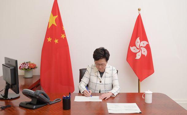 写真・図版 : 香港国家安全維持法を公布するため署名する林鄭月娥行政長官=2020年6月30日、香港、香港政府提供