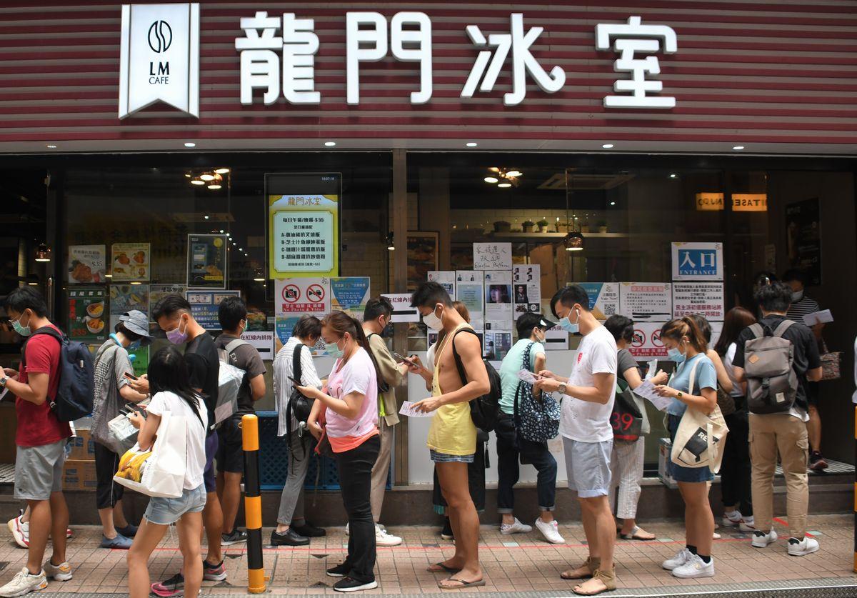 写真・図版 : 立法会選挙に向けた民主派の予備選挙の投票所となった飲食店の前に並ぶ市民ら=2020年7月11日、香港