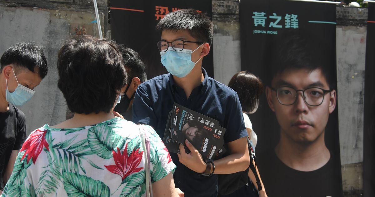 写真・図版 : 立法会選挙に向けた民主派の予備選挙の街頭演説で支持者と会話する民主活動家の黄之鋒氏(中央)=2020年7月11日、香港