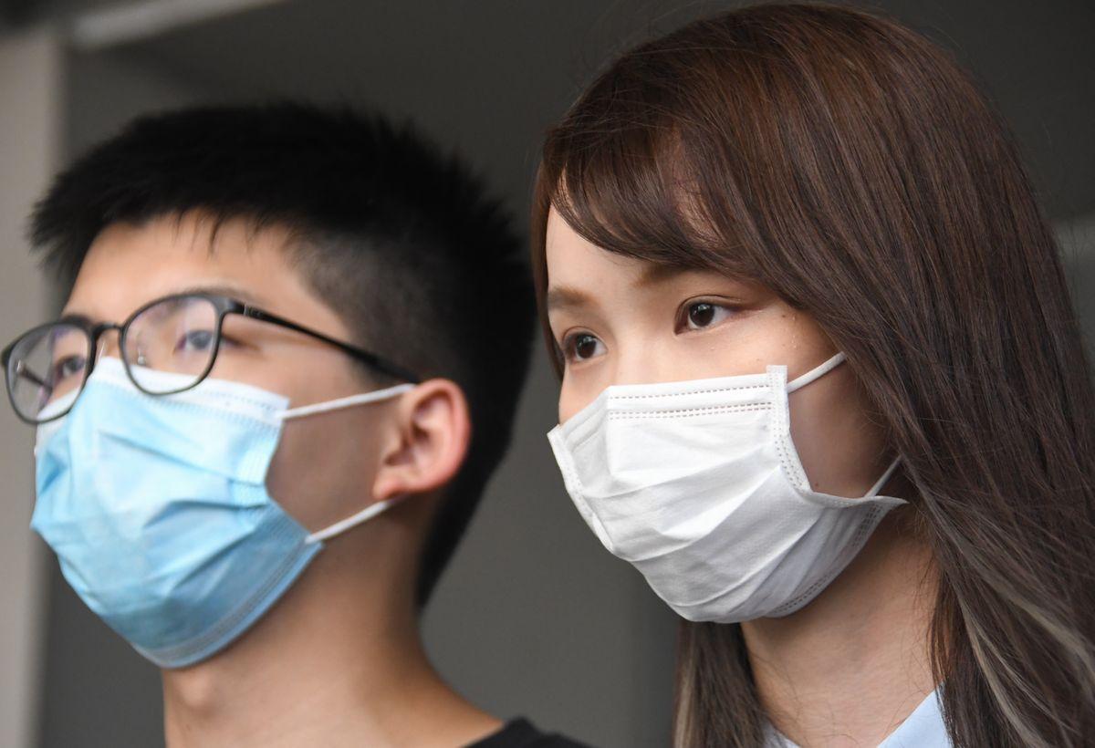 写真・図版 : 報道陣の取材を受ける周庭(アグネス・チョウ)氏(右)と黄之鋒(ジョシュア・ウォン)氏=2020年7月6日、香港