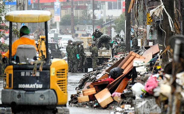 写真・図版 : 豪雨災害から10日あまりたった14日、熊本県人吉市では打ち付ける雨の中、片付けに追われていた=2020年7月14日午前9時57分、長沢幹城撮影