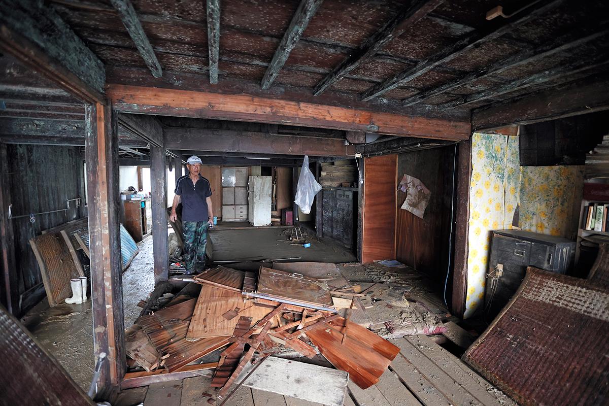 写真・図版 : 豪雨の被害により浸水した自宅の片付け作業に追われる住人の男性(79)=2020年7月13日、熊本県人吉市、藤原伸雄撮影