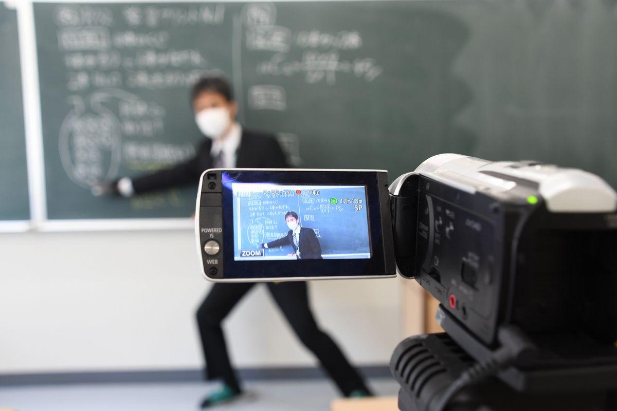 写真・図版 : カメラに向かって数学の問題を解説する広島皆実高校の教諭=2020年5月1日、広島市南区