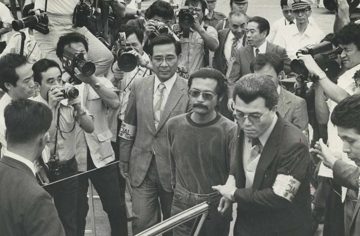 スウェーデンから強制送還された元立教大学助教授の高橋武智(中央) 1977年7月20日羽田空港