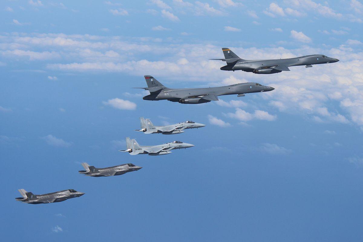 写真・図版 : 2017年8月に九州西方空域で行われた日米共同訓練。上の2機が米空軍のB1B、中央の2機が航空自衛隊のF15、下の2機が米海兵隊のF35B=空自提供