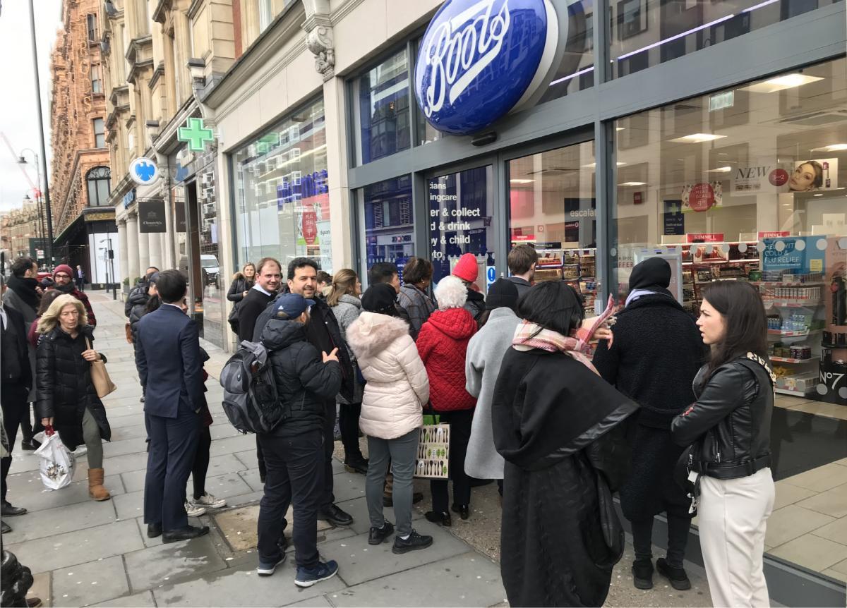 写真・図版 : 「手指の消毒剤が入荷したらしい」と聞いてロンドン中心部のドラッグストアに行列する人たち=2020年3月10日