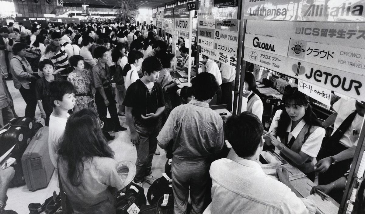 写真・図版 : 若者たちで混み合うパッケージツアーのカウンター=1992年8月、成田空港