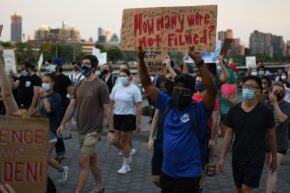 写真・図版 : フロイドさんの事件は目撃者によって撮影されていたこともあり、大きな波紋を呼んだ。抗議デモでは「撮影されていない事件はいくつあった?」というメッセージボードを持つ黒人男性の姿があった=2020年6月25日、米ニューヨーク、藤原学思撮影