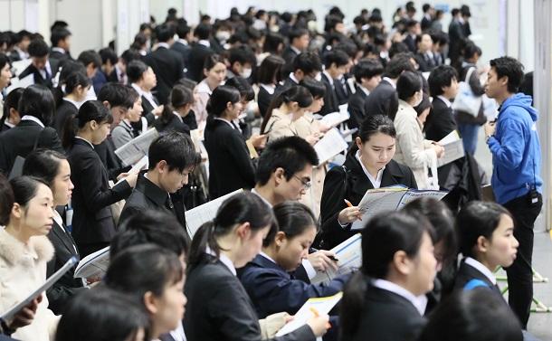 写真・図版 : 昨年の就職活動で各企業のブース前に並ぶ学生ら。今年はこのような説明会の中止が相次いでいる=2019年3月1日、大阪市