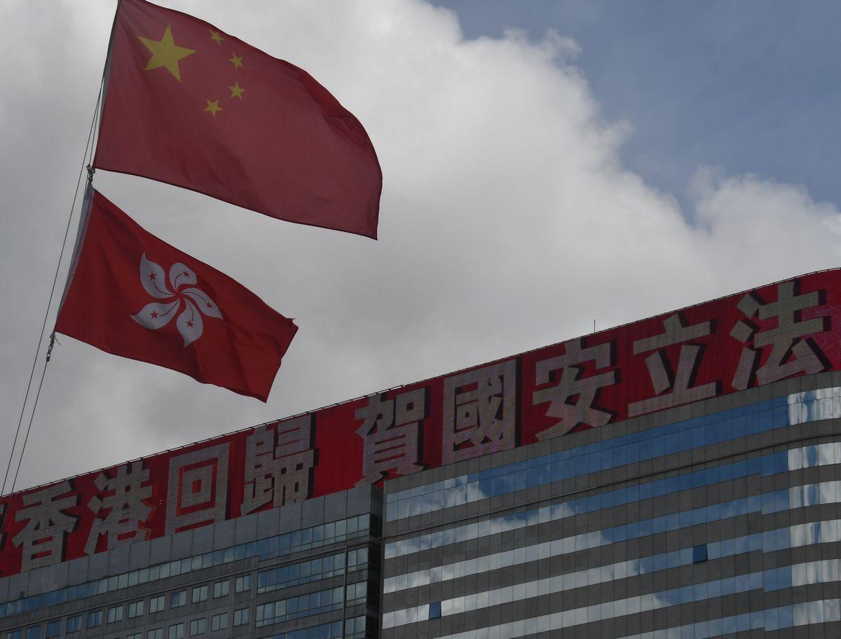 写真・図版 : 香港国家安全維持法の施行を祝う電光掲示板の手前で、中国の国旗(上)と香港の旗がはためいていた=2020年7月4日、香港、益満雄一郎撮影