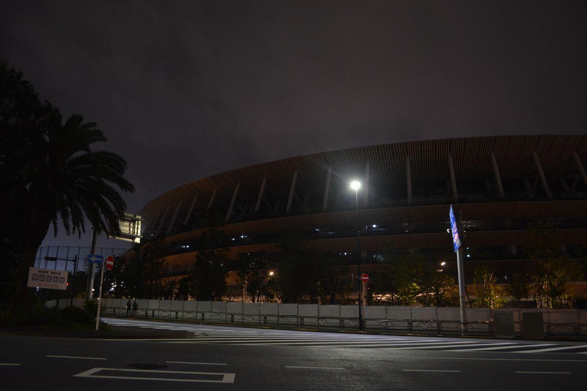 写真・図版 : 暗闇にひっそりと浮かぶ国立競技場=2020年7月24日午後8時52分、東京都渋谷区
