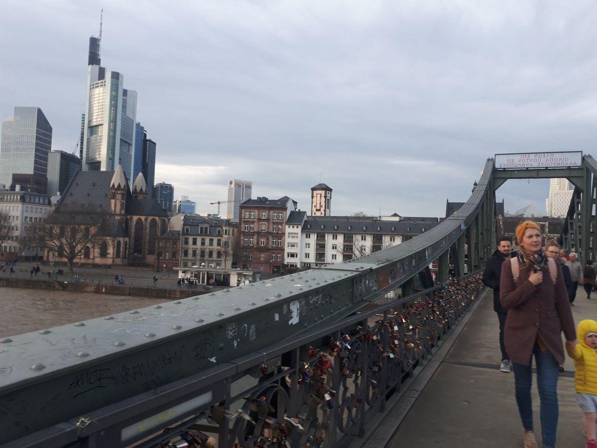 写真・図版 : マイン川にかかるウンターマイン橋。フランクフルトの高層ビル群も見える