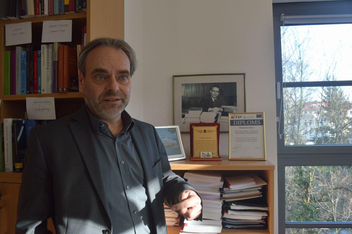 写真・図版 : インタビューに応じた国際教科書研究所のフクス所長。右後ろの壁に創設者エッカートの写真が掛かっていた
