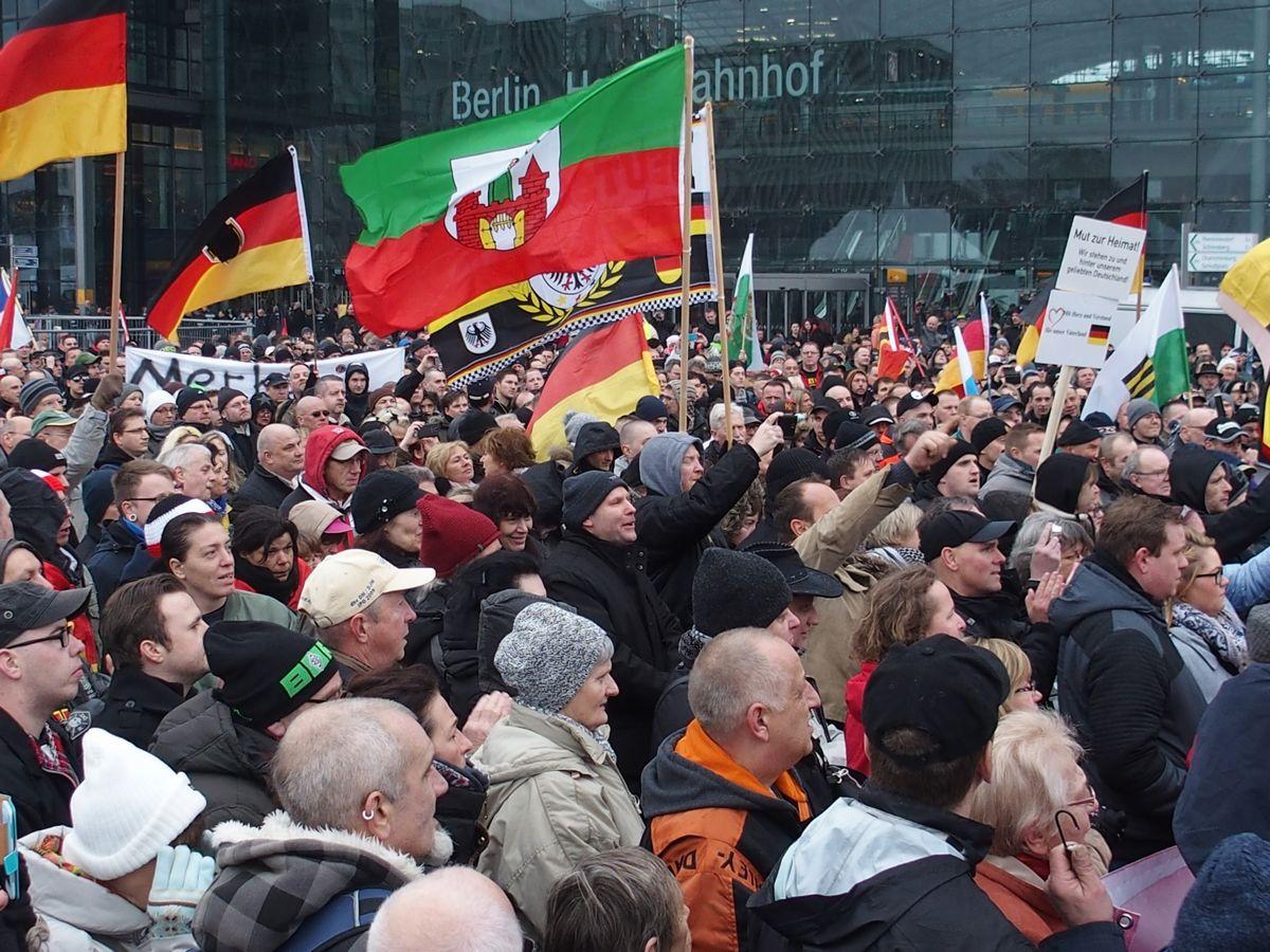 写真・図版 : ドイツで難民受け入れ反対のデモに参加する人たち=2016年、ベルリン中央駅前。朝日新聞社。