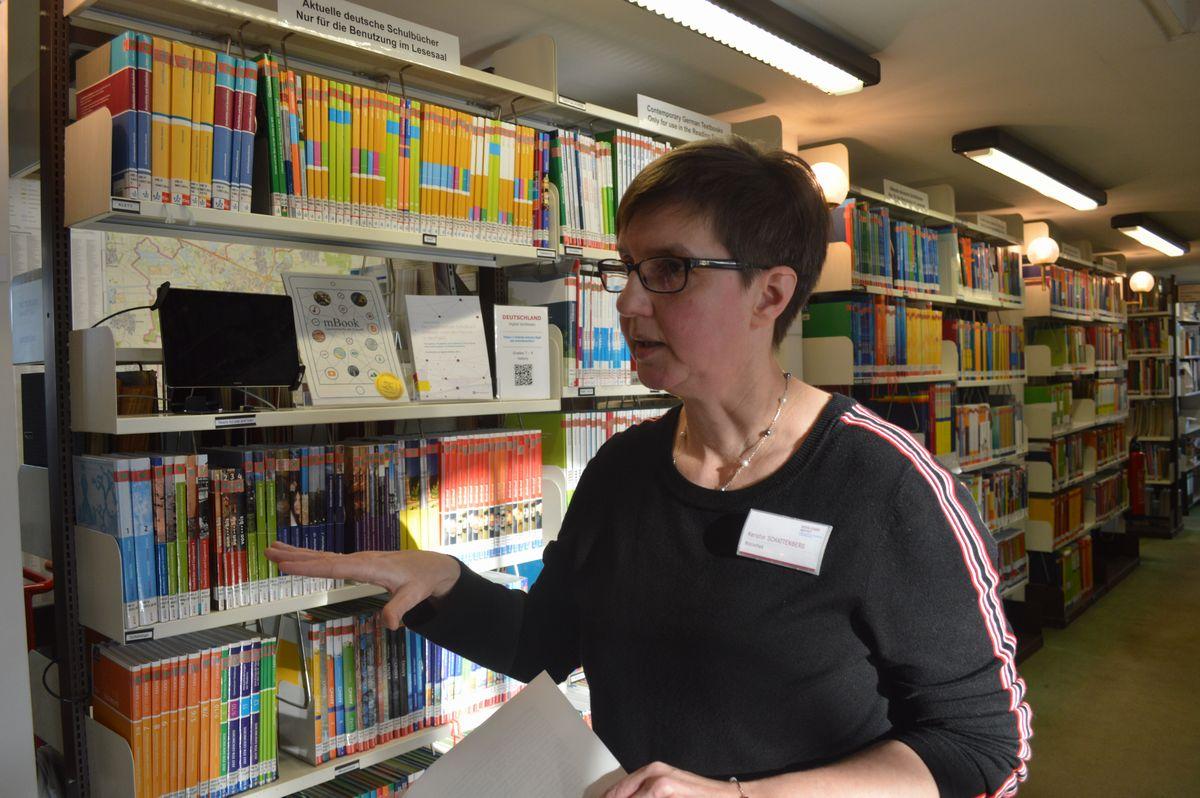 写真・図版 : ドイツの教科書がぎっしりと並ぶ国際教科書研究所の図書館で説明する司書=2月、ドイツ・ブラウンシュバイク。藤田撮影。以下同じ