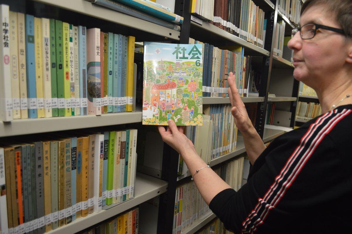 写真・図版 : 司書のシャッテンバーグさん。国際教科書研究所の書庫で日本の1社会の教科書を見せてくれた