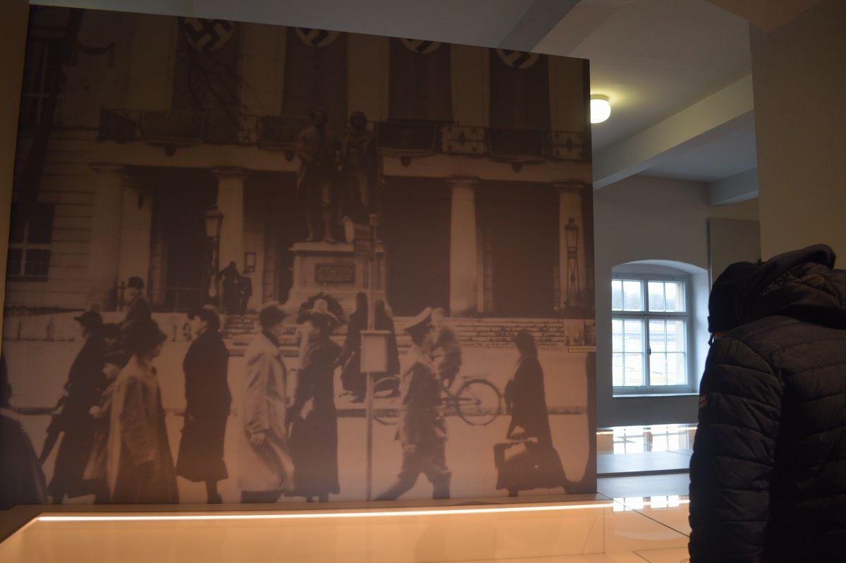 写真・図版 : 今もワイマール市街にある国民劇場に、ナチス時代にカギ十字の垂れ幕が掛かっている写真の展示
