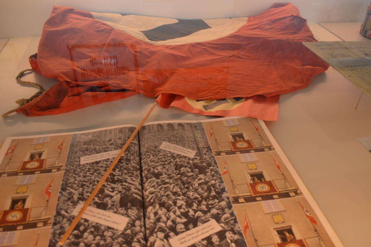 写真・図版 : 1938年にワイマールを訪れたヒトラーを歓迎する群集を紹介する印刷物と、その際に使われたとみられるカギ十字の幕