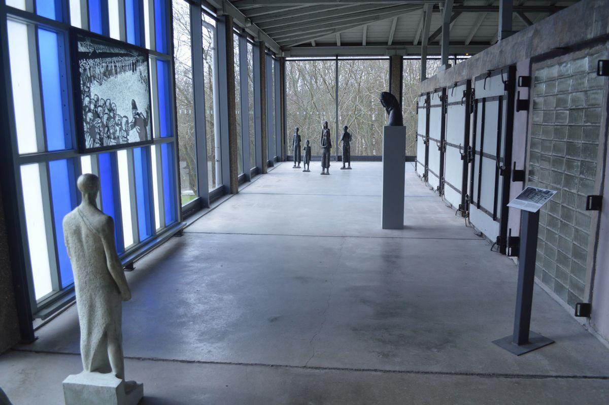写真・図版 : 収容者たちからはぎ取った服などを消毒した房が並ぶ(右側)部屋に、像や版画(左側)の作品がある