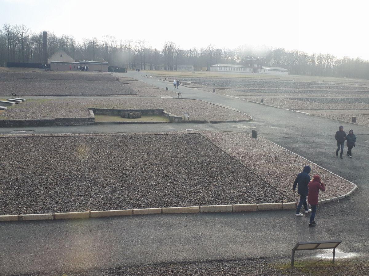 写真・図版 : 強制労働にかり出された収容者たちが住んだバラックは、今は跡形もない.。奥の煙突の建物は遺体焼却場=2月、ドイツ・ワイマール。藤田撮影。以下同じ