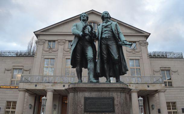 写真・図版 : ワイマール憲法が採択された国民劇場の前に建つ、当地ゆかりの文豪ゲーテとシラーの像=2月、ドイツ・ワイマール。藤田撮影。以下同じ