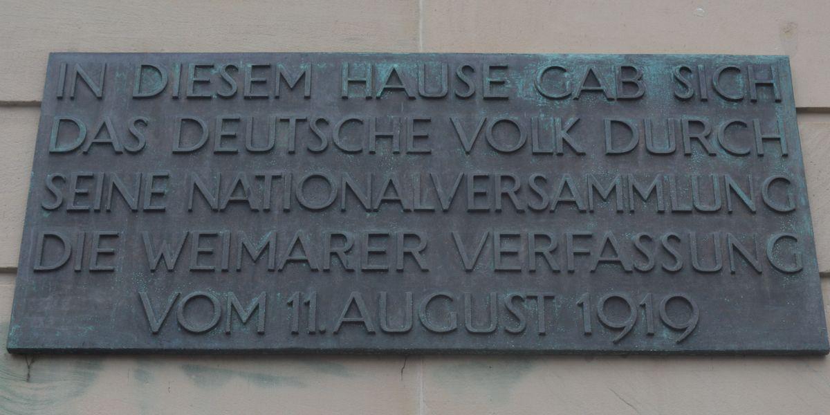 写真・図版 : 国民劇場の壁にある、1919年にワイマール憲法がここで採択されたことを記す碑文