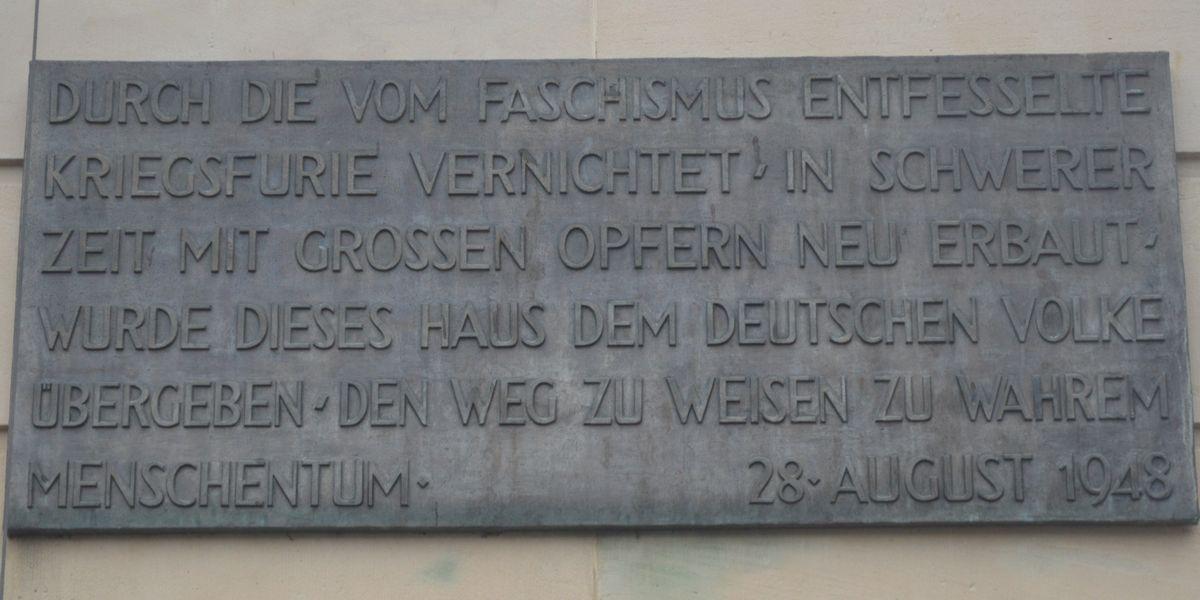 写真・図版 : 国民劇場の壁にある、「ファシズムによる破壊」から1848年に再建されたことを記す碑文