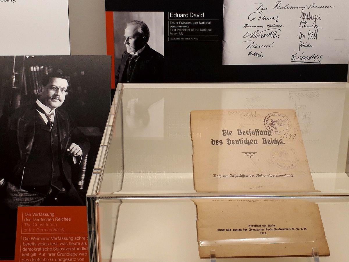 写真・図版 : 1919年に採択されたワイマール憲法の冊子と、作成に携わった人たちの展示